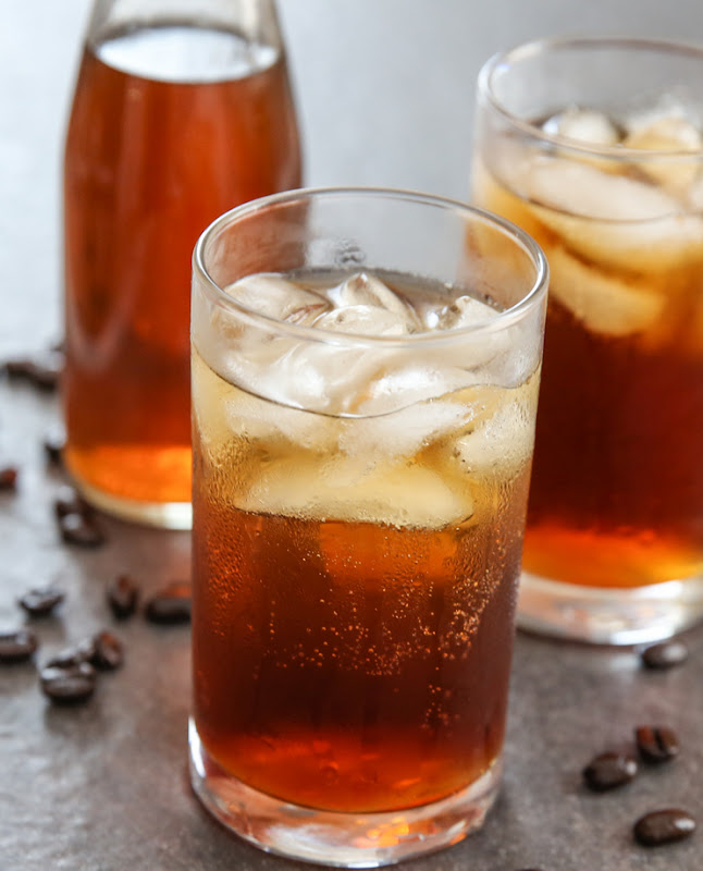 photo of a glass of Coffee Soda with a glass and jug in the background
