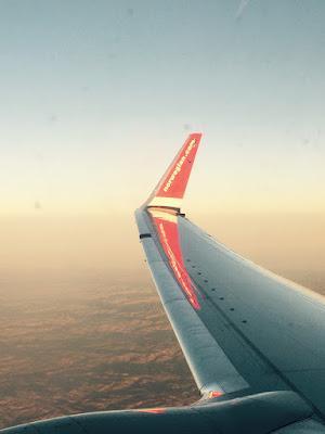 En flyvinge over et landskap i solnedgang.