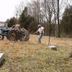 George appears to pull the tractor.  For posts in the ground so deep that they could not be pulled out by hand, George placed two log chains around the post.  Then while Owen drives the tractor to pull out the post, George holds the chains out of the way of the tractor tires.