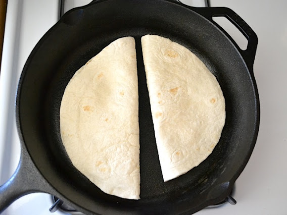 two quesadillas cooking in skillet