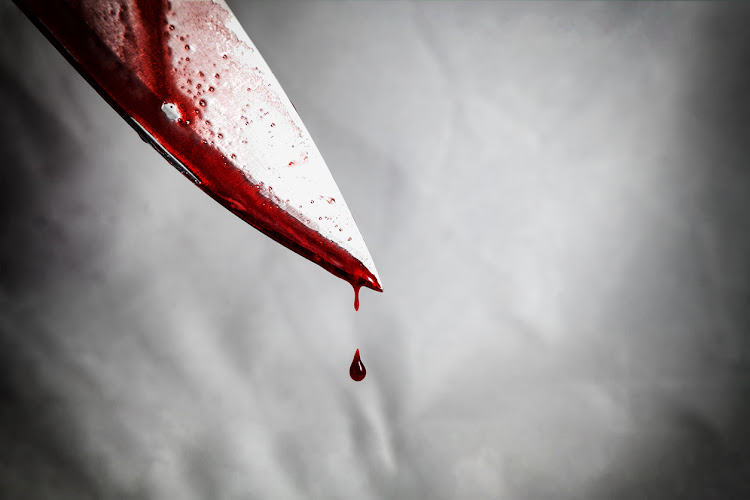 Close-up of man holding knife smeared with blood and still dripping. File photo.