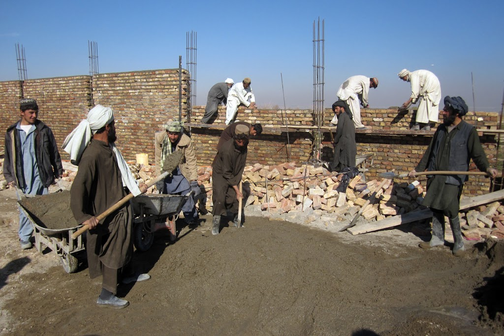 Workers building with recovered bricks from the first GVS school