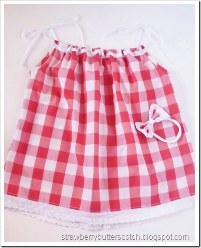 Red and white gingham print pillow case dress for baby, with matching headband.