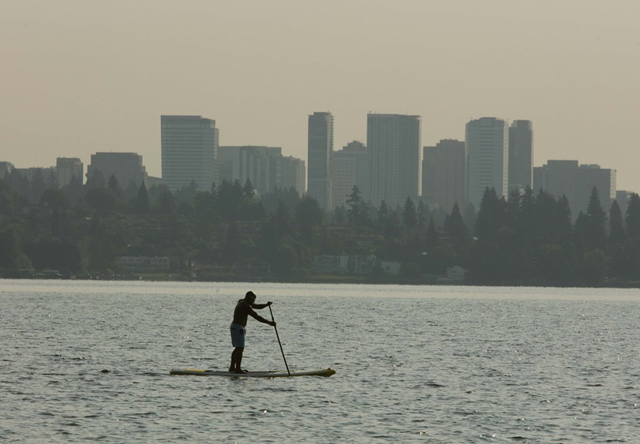 Smoke from fires near Cle Elum obscures the Cascades as a paddle boarder on Lake Washington glides past the hazy horizon including the Bellevue skyline on Monday, 28 August 2017. Photo: Steve Ringman / The Seattle Times