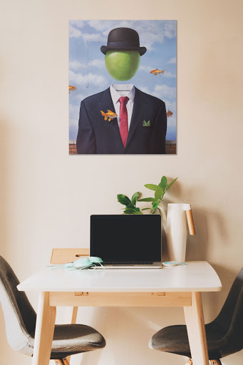 Painting by Paul Bond hangs above simple work desk