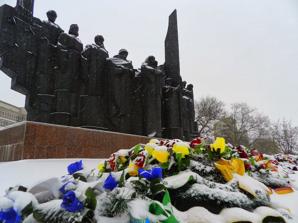 snow-covered flowers in front of this huge monument
