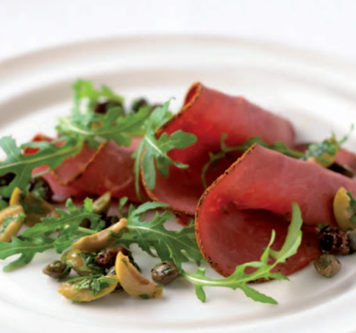 Sliced beef and arugula salad with green olive and raisin salsa