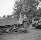 Citizen of Aalst carrying an orange flag is handing out cigars to British soldiers traveling in Bren carriers. Date: September 18, 1944. Photographer: Willem van de Poll. Source: Dutch National Archive