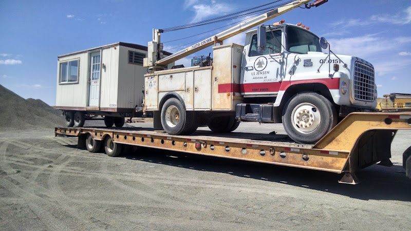 white utility truck and trailer loaded on a flatbed trailer
