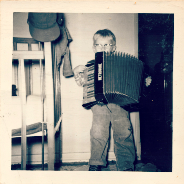 Rene Fabre playing accordion in the bedroom. Renton Highlands circa 1954.