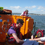 Crew members Oli Mallinson and Rob Inett care for a casualty with a back injury aboard the ALB in Poole Harbour - 5 May 2013. Photo credit: RNLI/Dave Riley