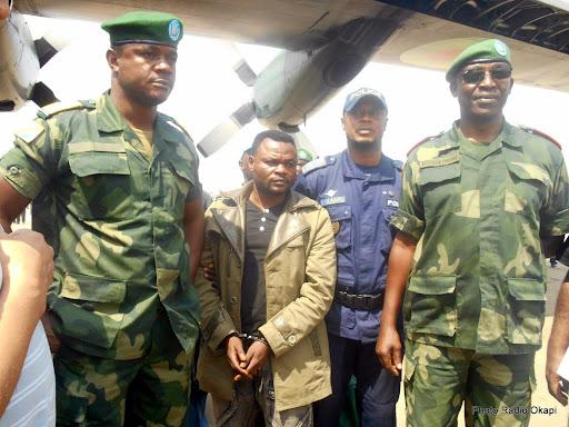Sous escorte militaire et menotté, Cobra Matata arrive aux pieds de l'avion qui le transporte de Bunia à Kinshasa, lundi 5 janvier 2015. Photo Radio Okapi/Martial Kiza