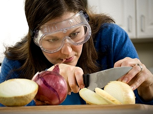 Close-up of a mid adult woman cutting an onion