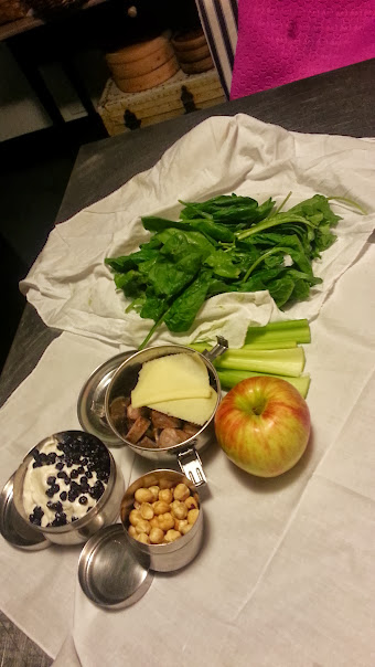 The lunch containers opened to show yogurt and blueberries, meat and cheese, nuts, and spinach