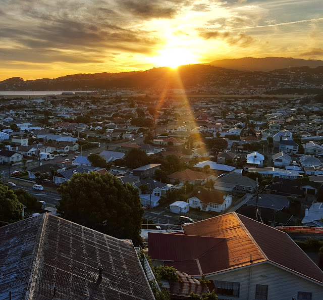 Photo of sunset beam striking roof across the hills of Wellington