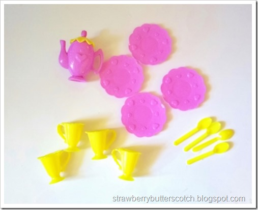 A pink and yellow plastic toy tea set bought from Dollar Tree, a dollar store chain.