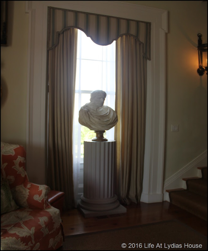 foyer bust on pedestal at foot of stairs