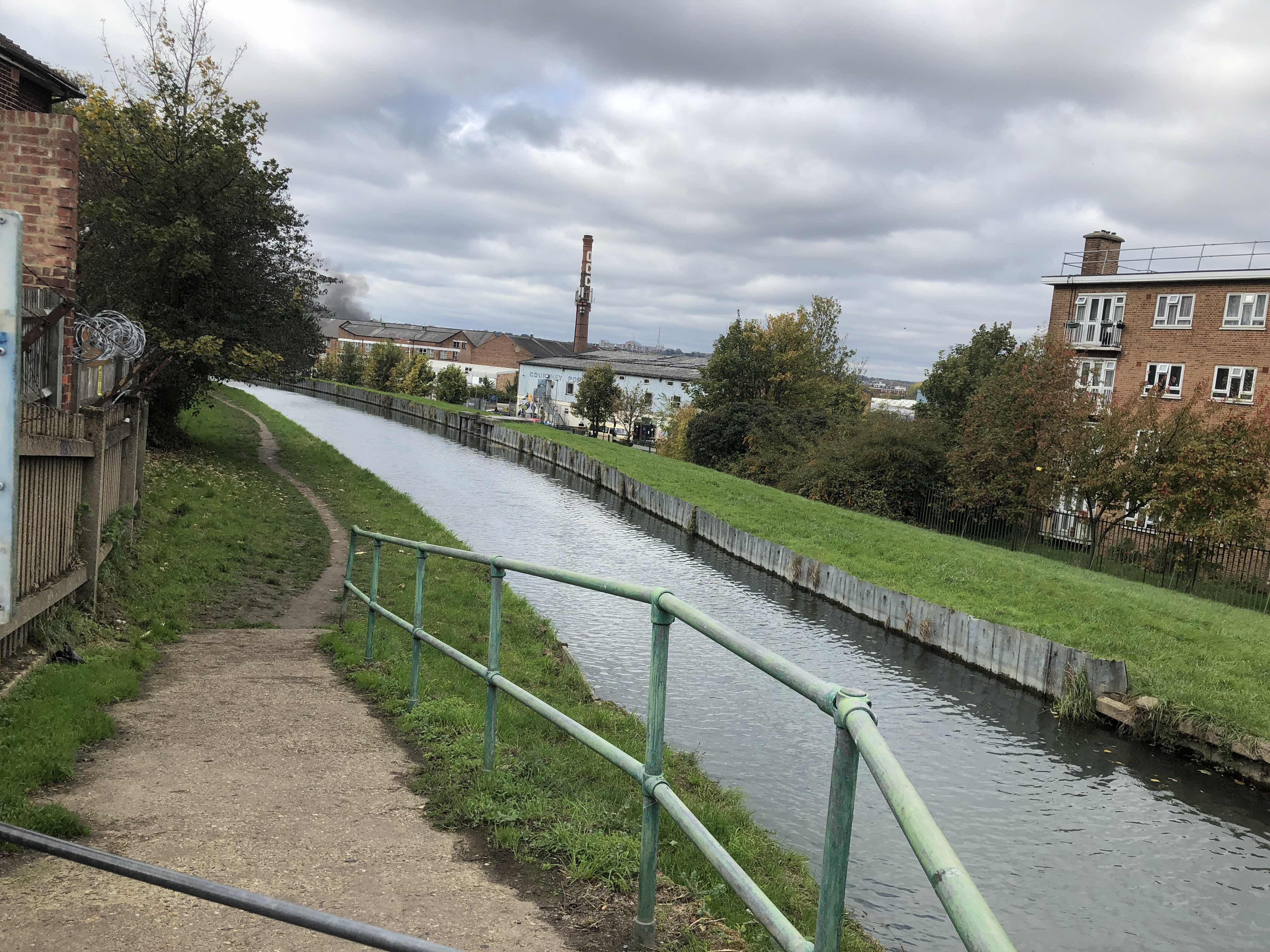 A view of the New River which, at this point, is a straight and narrow body of water stretching into the distance. To the left of the picture can be seen the entrance to its towpath.