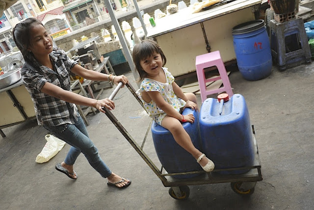 little girl sitting on a jug on a cart being pushed by a young woman at a market in Phnom Penh