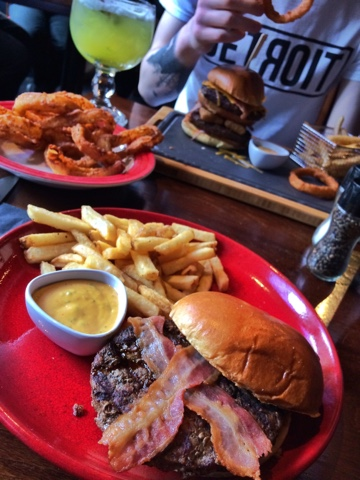Colse up on a plate of food from TGI Fridays. There is the classic american burger with bacon and a side of onion rings.