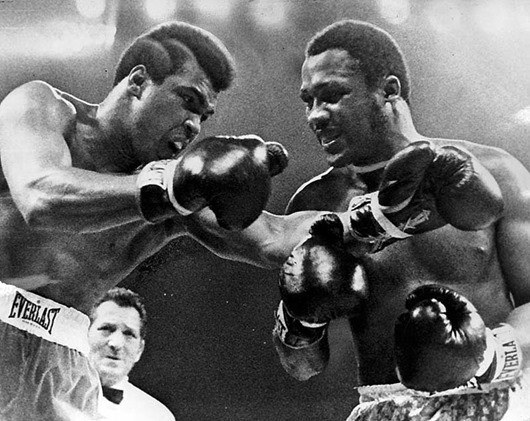 Joe Frazier, right, appears to be smiling as challeger Muhammad Ali misses with a left in the title fight. (March 1971)