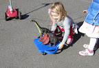 Child pushes a scooter board to carry three large dinosaur toys on the playground.