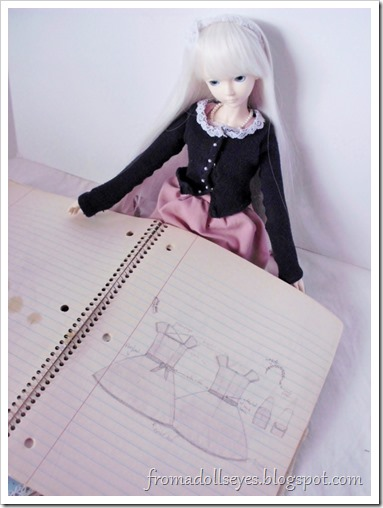 A ball jointed doll looking at clothing designs in a notebook.