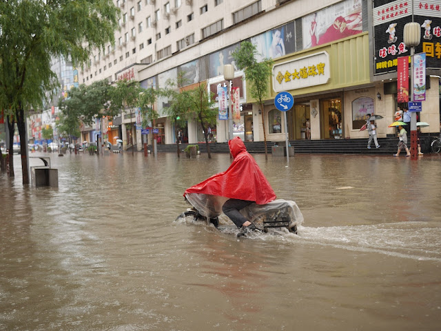 man riding a motorbike on a flooded street in Taiyuan, China