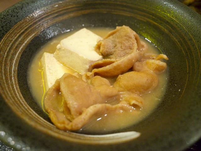 皿に盛られた、もつ味噌煮込み豆腐