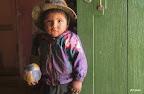 Un jeune Bolivien s'étonne de voir passer un voyageur à pied sur le seuil de sa maison.