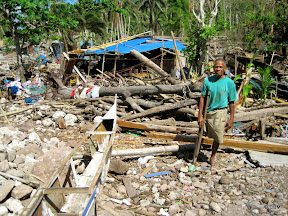 A man (above-knee amputee, using crutch) standing amidst rubble
