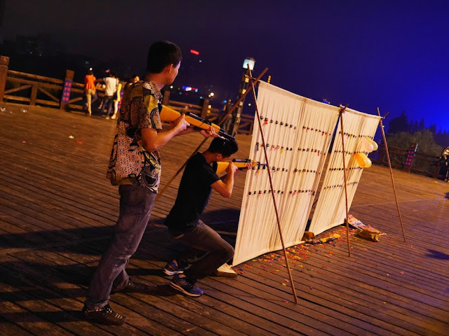two men shooting balloons from the side at night in Hengyang, China