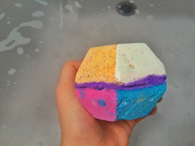 Close up photo of The Experimenter bath bomb by Lush in a girls hand