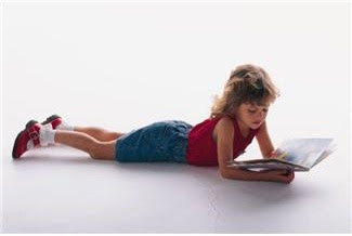 Girl about 7 years old lying on floor reading