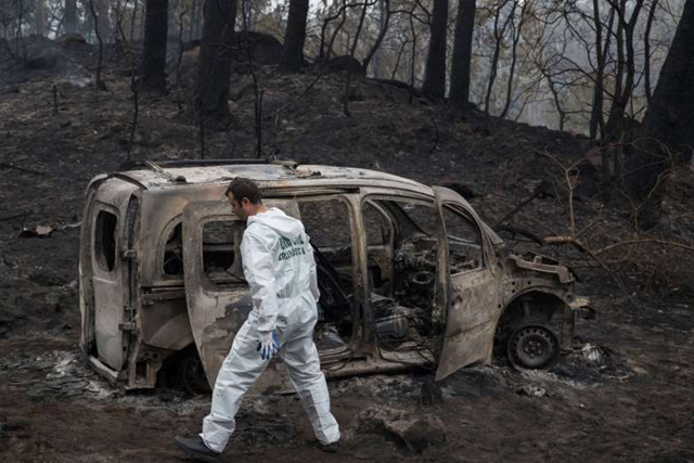 Scientist Police inspects the remains of the car where two women died after a wild fire in Pontevedra, in the northwestern Spanish region of Galicia, Spain, Monday, 16 October 2017. Authorities in Portugal and Spain say that hundreds of wildfires fanned by strong winds have caused multiple deaths as people got trapped by fast moving fires. Photo: Lalo R. Villar / AP Photo