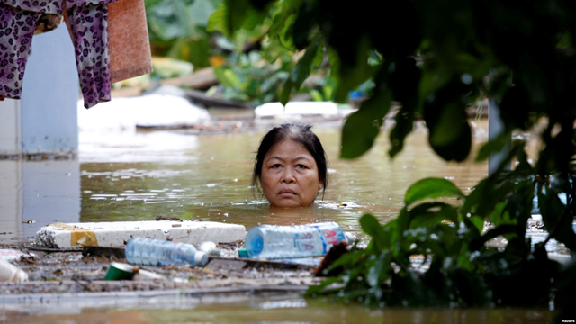A woman wades through a submerged street at the UNESCO heritage ancient town of Hoi An after typhoon Damrey hits Vietnam, 6 November 2017. Photo: Reuters