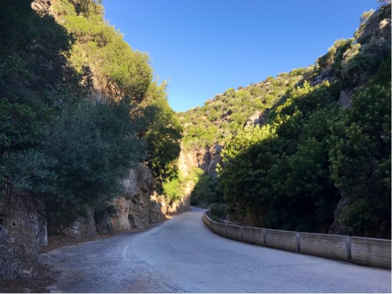 En smal vei som svinger seg mellom noen grønne fjellsider.