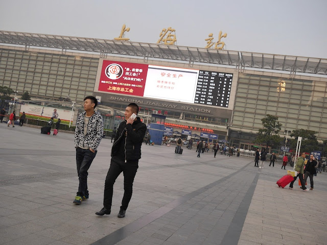 two young men walking front of the Shanghai Railway Station