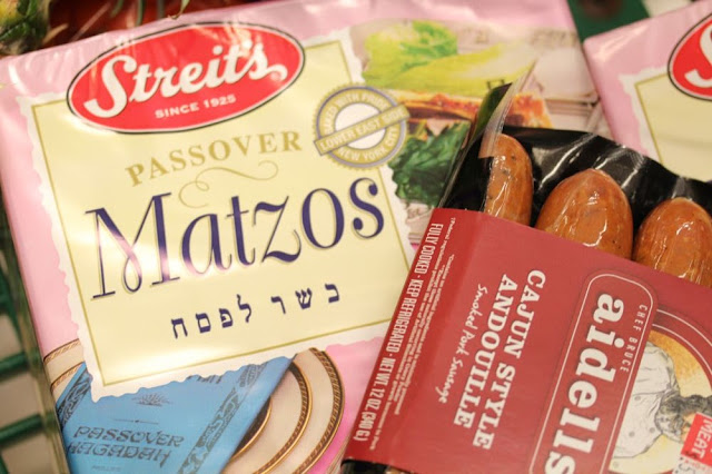 a box of matzah and a package of pork sausage in a grocery cart