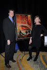 "Bryan and Trish Biddle pictured with ""Venice Bridge,"" an original oil painting by Trish, donated to the auction. The painting was won by Tommy and Shelly Cunningham Photos taken by Kristina Bowman"