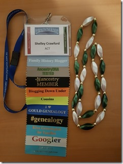 Conference tag with ribbons attached, string of beads.