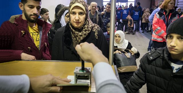 In Germany, a UN resettlement programme gives families hope. Here, an immigration officer stamps the passports of a Syrian family that has just landed at Hanover airport on a charter flight from Egypt. Photo: Gordon Welters / UNHCR