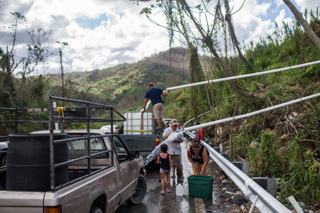 People in Puerto Rico cluster along roadways to bathe and do laundry using water sent down from higher elevations in PVC pipes. Some collect water to take home, for flushing toilets and cleaning. Photo: Dennis M. Rivera Pichardo / The New York Times