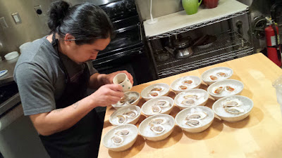 Colin Yoshimoto carefully adding mignonette to the oysters