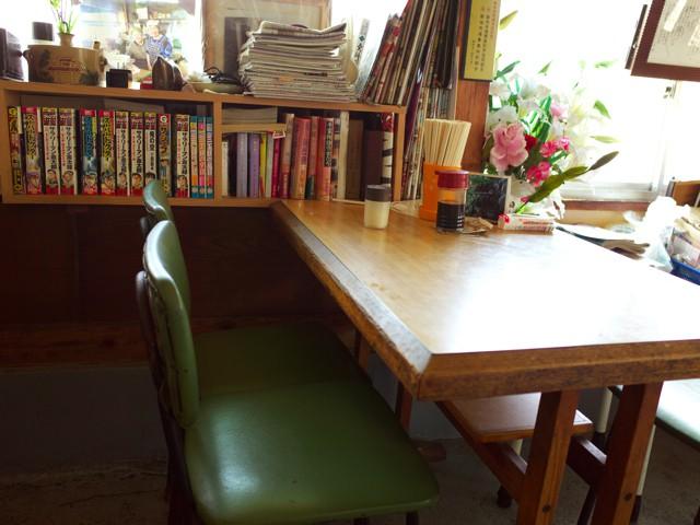 店内のテーブル席と漫画のある棚