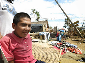 A young man in a wheelchair amid destroyed buildings, fallen power lines and drying clothes