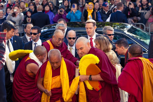 His Holiness the Dalai Lama arriving at Kurukulla Center being greeted by Lama Zopa Rinpoche (front center), Sikyong Lobsang Sangay (far left), Geshe Tenley (left of Rinpoche) and others, Kurukulla Center, Medford, Massachusetts, U.S., October 2012. Photo by Kadri Kurgun.