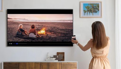 A person tapping their phone to the samsung TV and mirroring a video of people on the beach