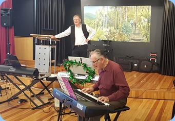 Roy Steen playing his Korg Pa300 whilst our host, Len Hancy, watches on.