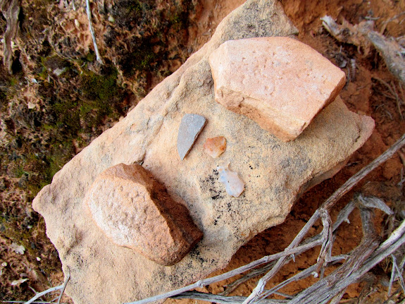 Metate fragments, pottery, and chert in the alcove near the natural bridge